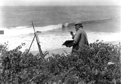 Artist Frank Cuprien painting an ocean view from cliffs at Laguna Beach.